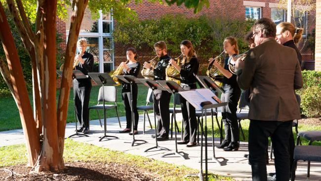 7 UMD students standing in a row playing French horn with music stands, led by a UMD professor also playing horn.