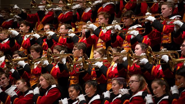 marching band members in rows wearing red, black, gold, and white uniforms and white gloves as they play various horns.