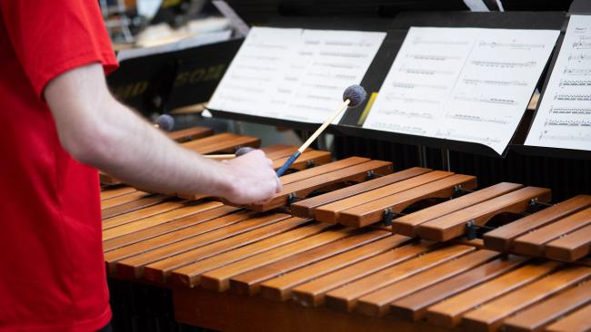 a close-up marimba being played by a UMD student and a music stand with their music.